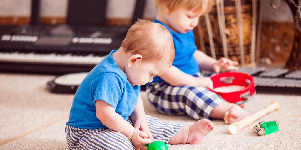 Two toddlers playing with percussion instruments