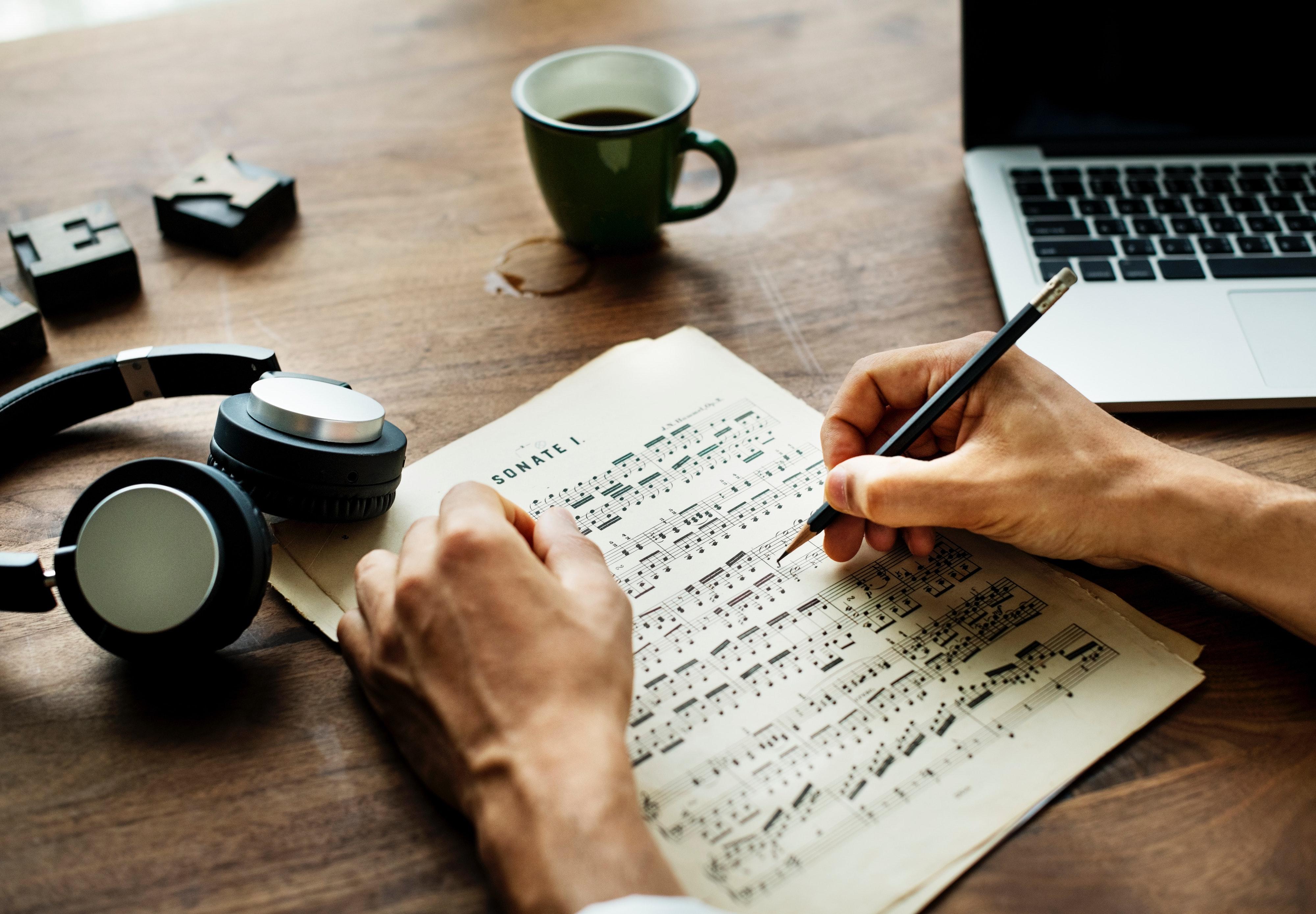 Person skriver på nodepapir. Kaffekop, laptop og høretelefoner også synlige.