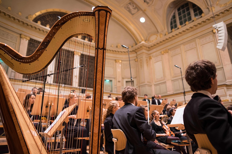 Orkester, med harpe i forgrunden