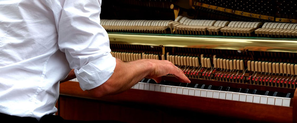 Mand der spiller på opretstående klaver