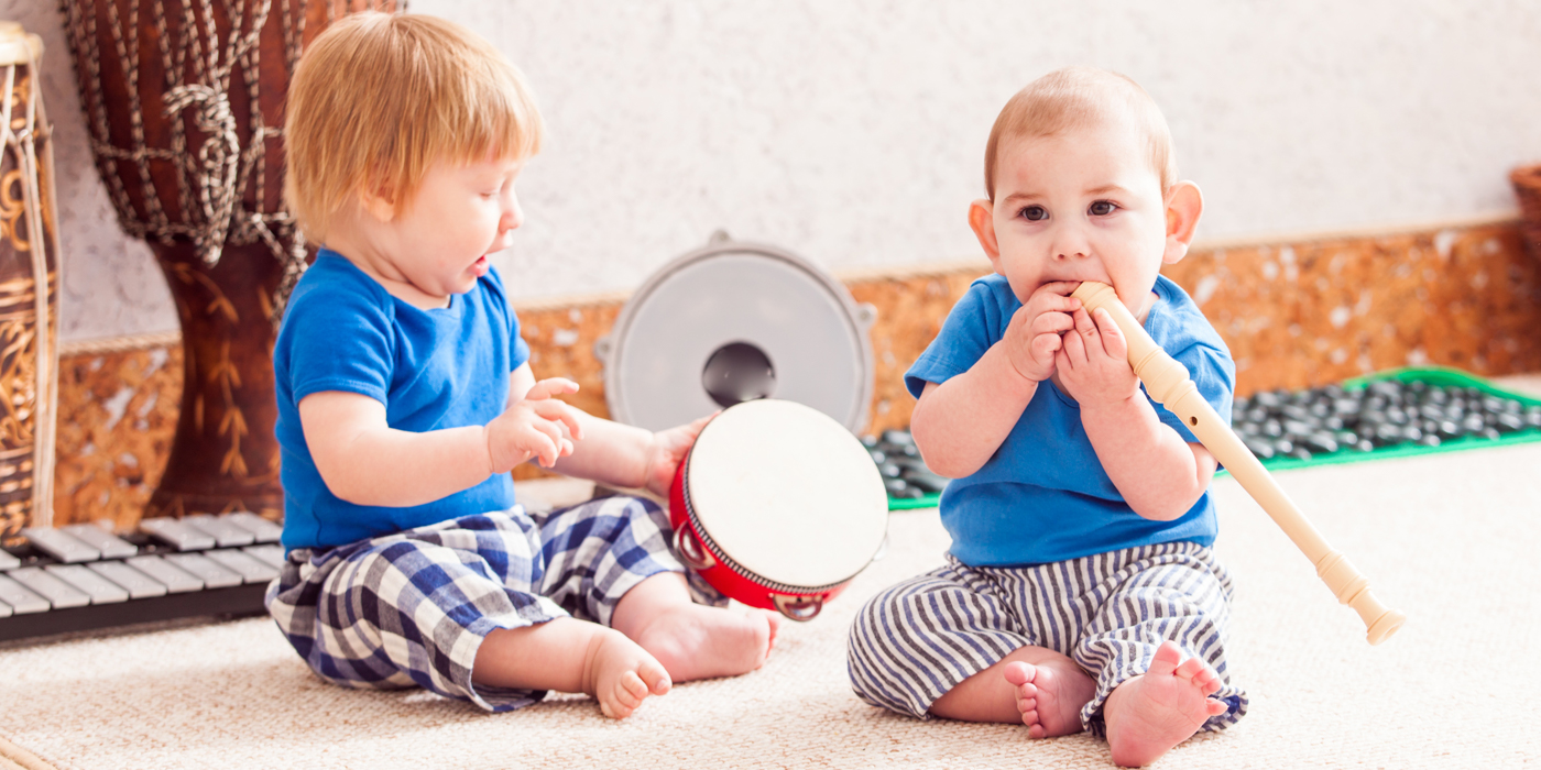 Two toddlers playing with instruments
