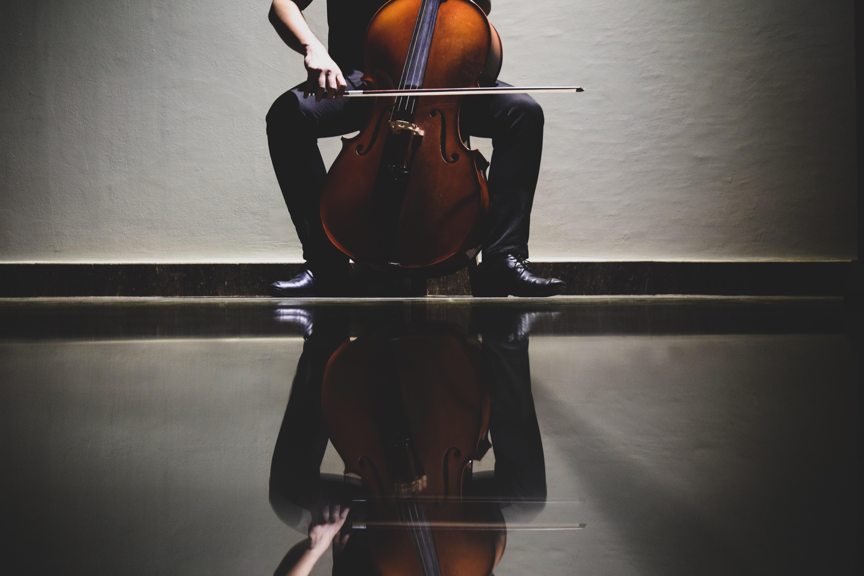 Musikant med cello, afspejlet i gulvet