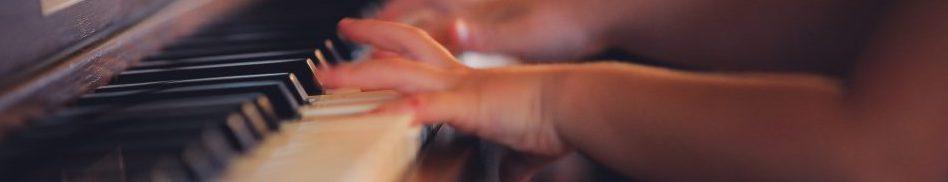 Close-up af børnehænder der spiller klaver