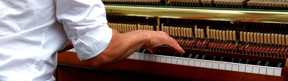 Hands of man playing upright piano